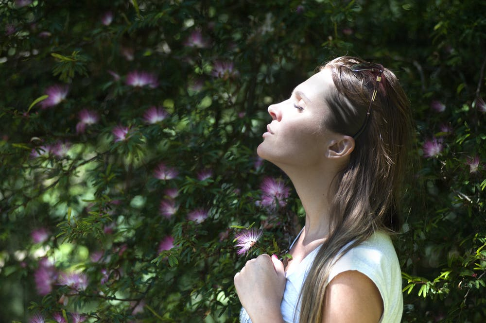 Woman outside smelling flowers