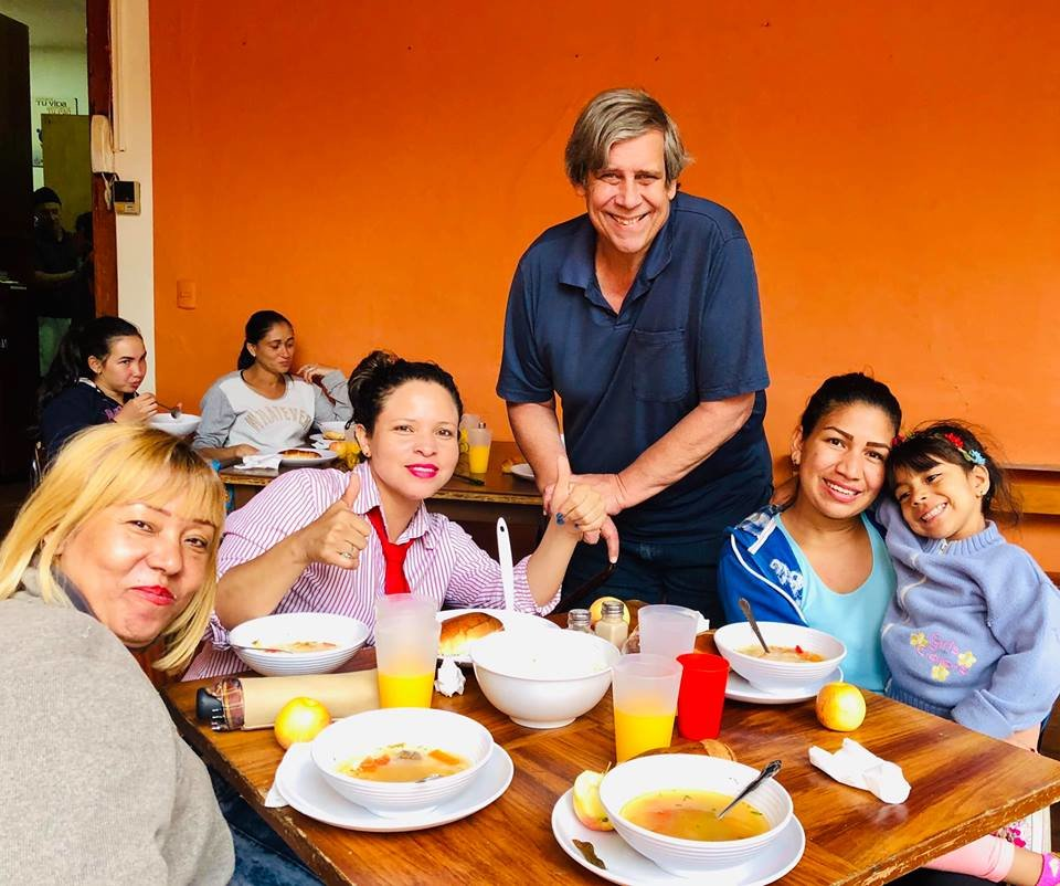 Bob Higgins, Executive Director and Founder of the Cuenca Soup Kitchen, serving a hungry Venezuelan family a hot lunch.