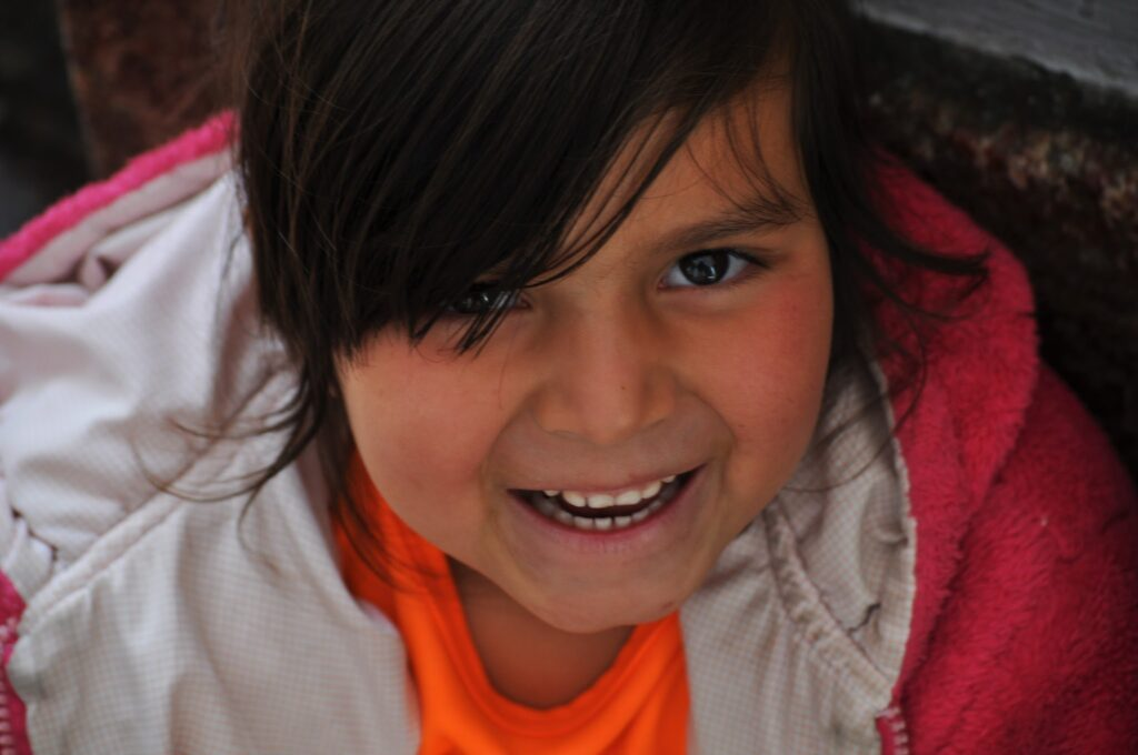 Little Ecuadorian girl showing off her beautiful smile to the camera in Cuenca, Ecuador.