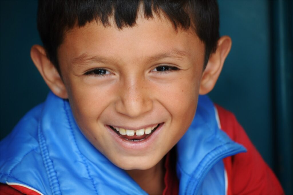 A young Ecuadorian boy showing off his winning smile in front of the The Cathedral of the Immaculate Conception.