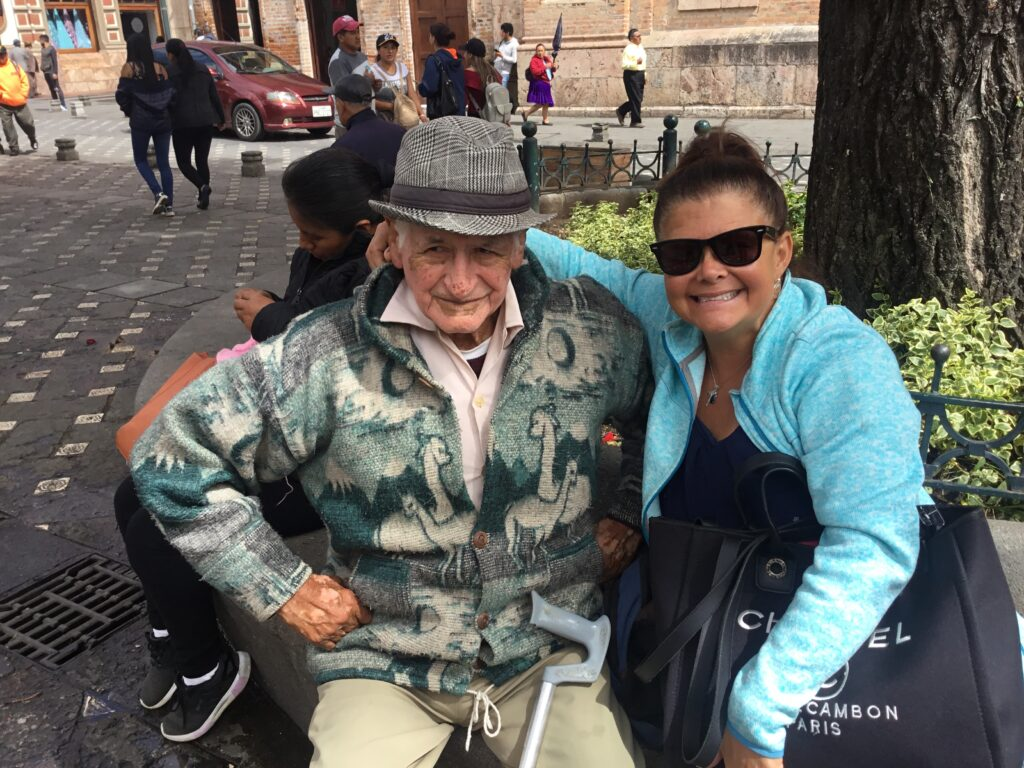 Kathleen Rodas sits and chats with one of our clients Victor in the Plaza de las Flores in Cuenca, Ecuador.