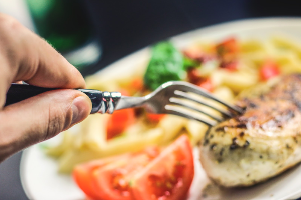 a fork poking into a dinner of chicken and vegetables