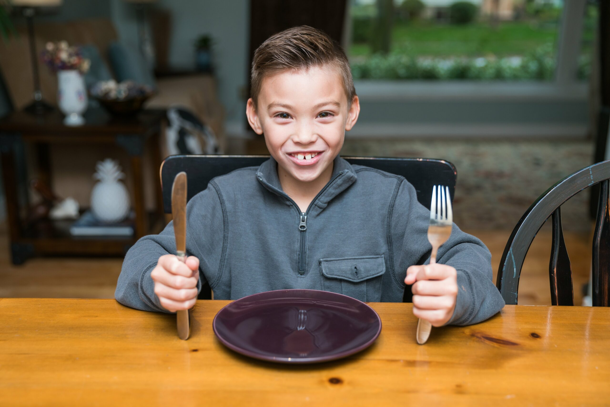 picture of kid holding cutlery in front of plate