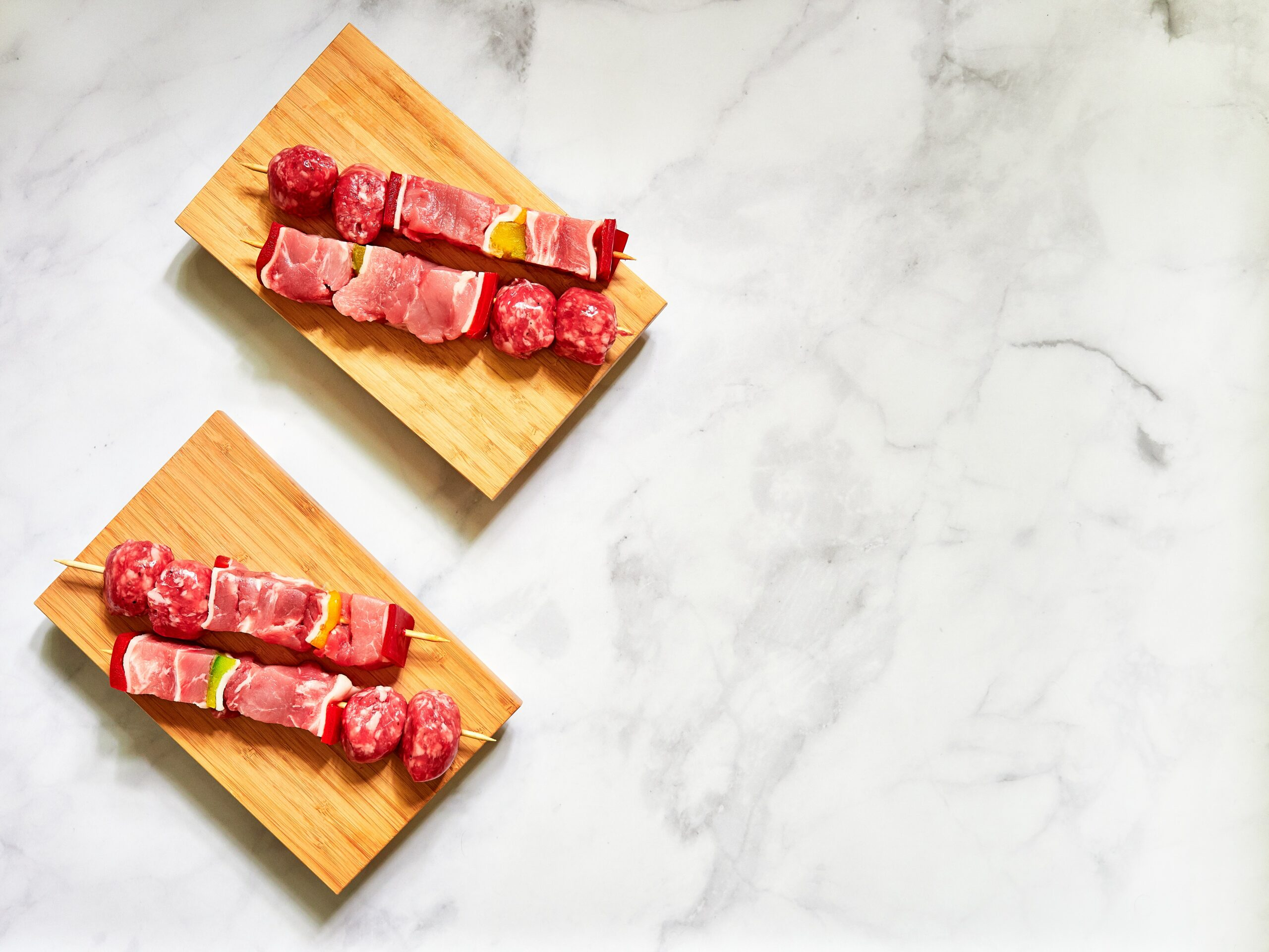 picture of raw meat skewers on board on top of marble slab