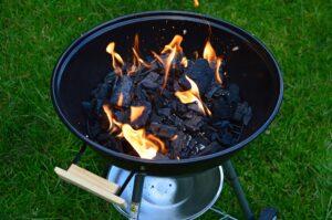 picture of charcoal smoker outside with lit flame