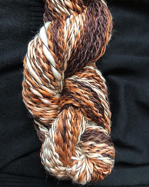 A twisted skein of handspun wool yarn in shades of cream, fox orange, and walnut brown. The wool has been plied with dark brown sewing thread.
