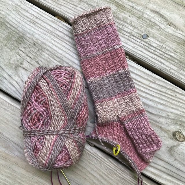 Partially-completed hand-knit sock in marled rose and greyish-brown tones.