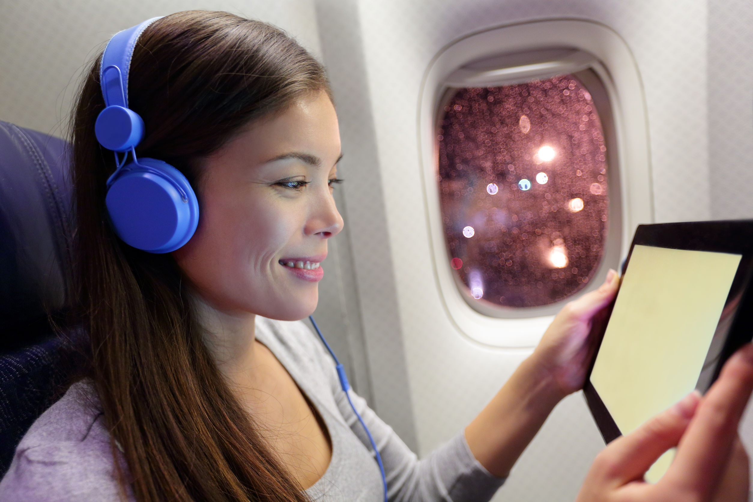 32105389 - passenger in airplane using tablet computer. woman in plane cabin using smart device listening to music on headphones.