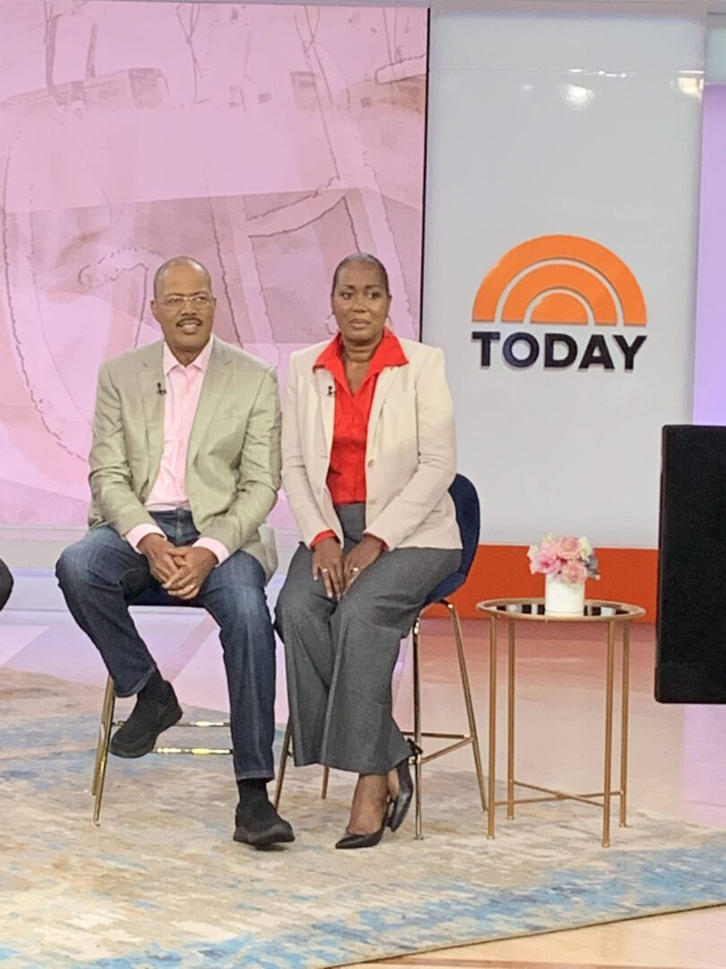 Two people sitting on a tall chair on a stage of a talk show
