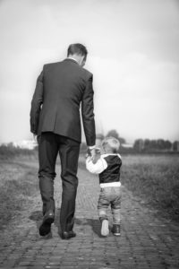 Dad and son walking side by side holding hands