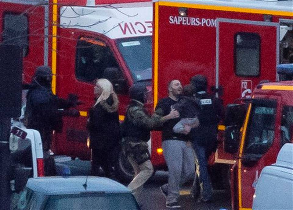 ALTERNATE CROP OF XPDA123 - A security officer directs released hostages after they stormed a kosher market to end a hostage situation, Paris, Friday, Jan. 9, 2015. Explosions and gunshots were heard as police forces stormed a kosher grocery in Paris where a gunman was holding at least five people hostage. MICHEL EULER AP PHOTO