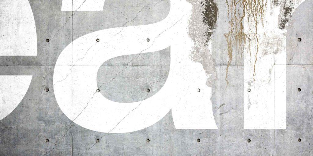 Helvetica Now font on concrete