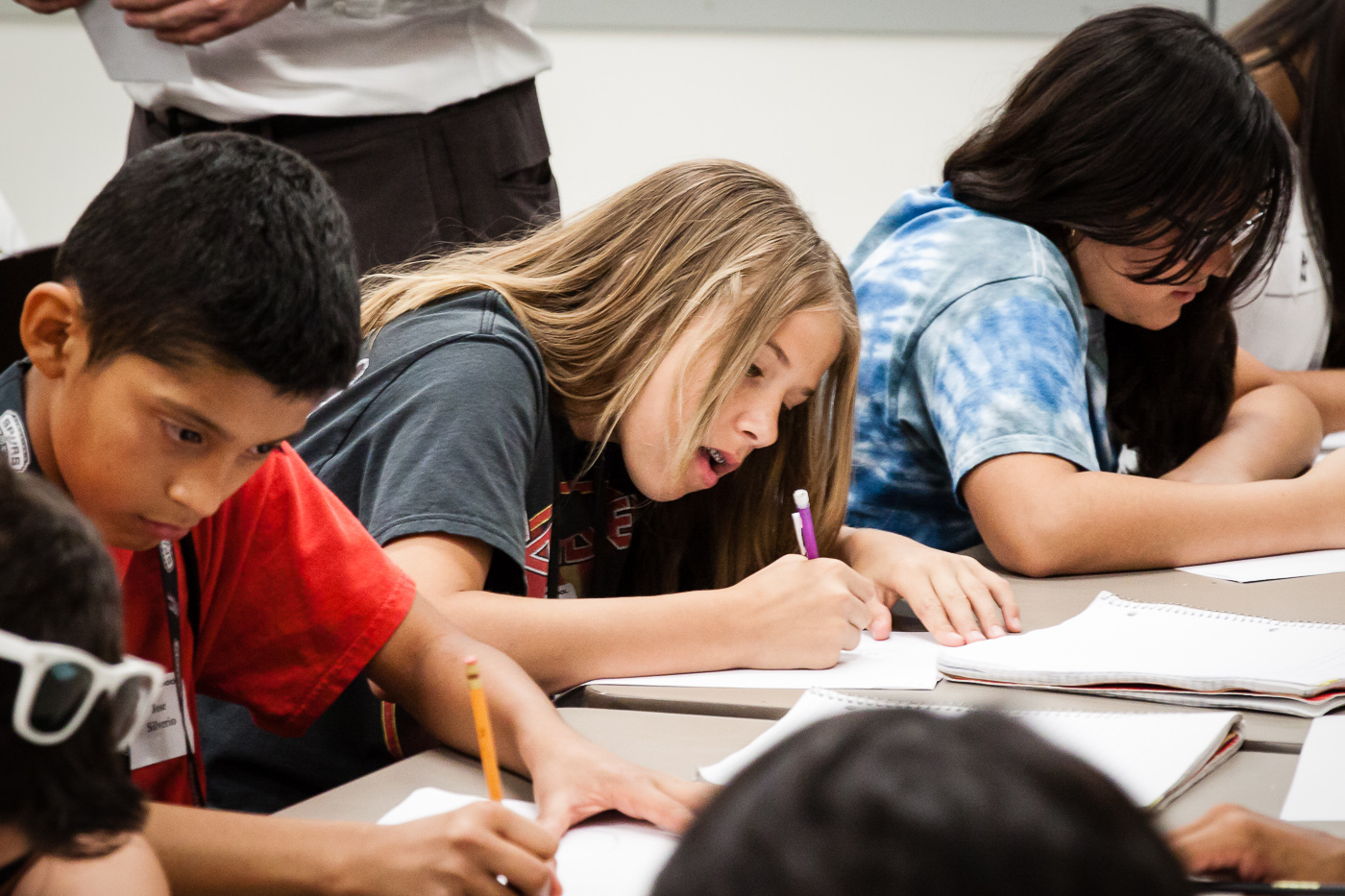 Students Writing On Paper In Classroom