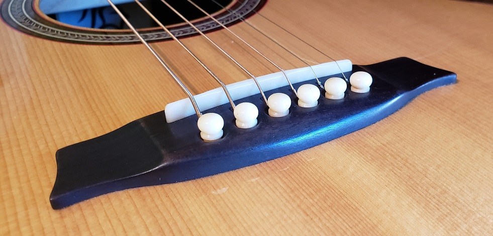 Why Some Guitar Brands Use Plastic Saddles Instead of Bone