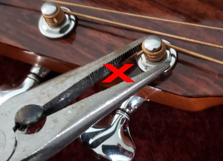 Incorrect way of tightening tuning machines by using needle nose pliers.