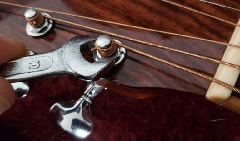 Guitar tuning machines being tightened with wrench