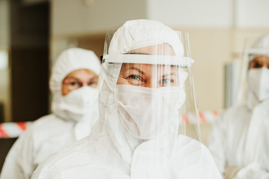 Nurse in full protective gear smiling behind mask.