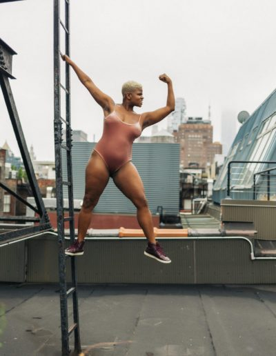 Ericka Hart on a ladder on a rooftop
