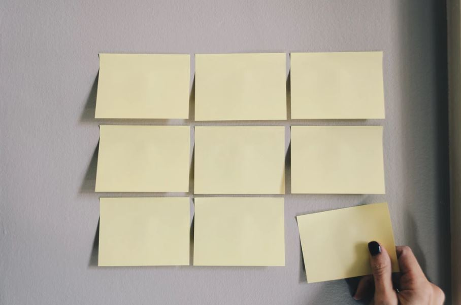 Blank post-it notes on a board and a woman's hand moving one note.