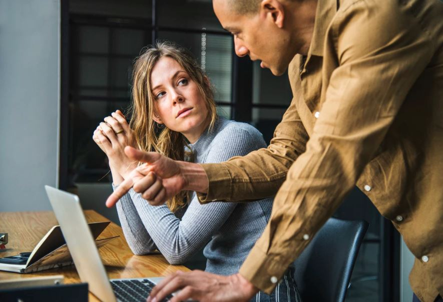 Male and female coworkers discuss work over a laptop.