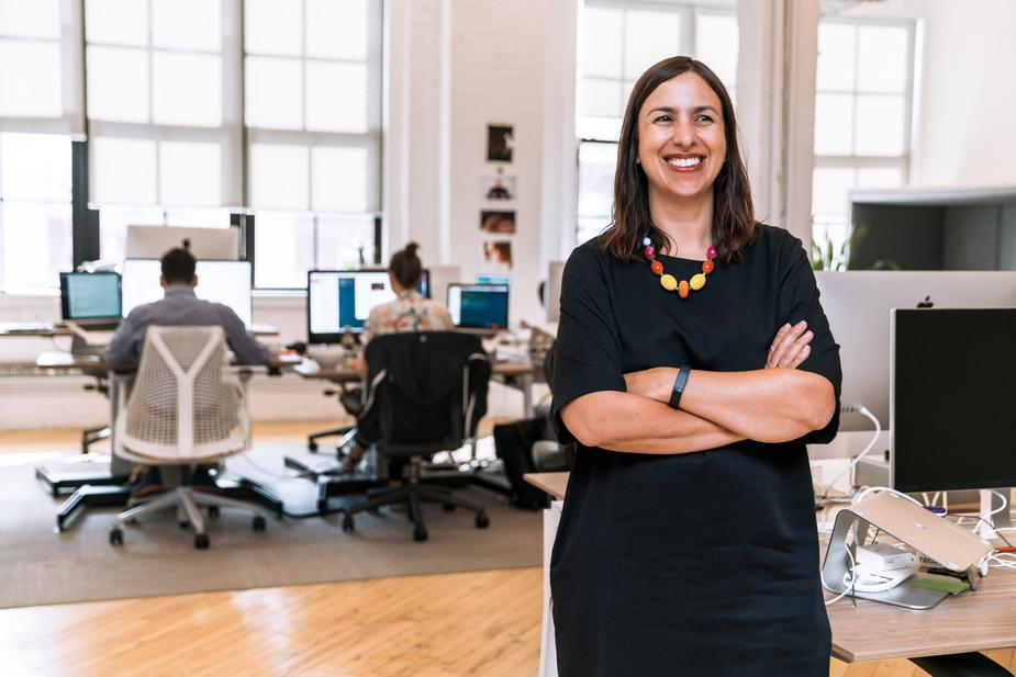 A smiling business woman standing in front of a row of employees working on computers.
