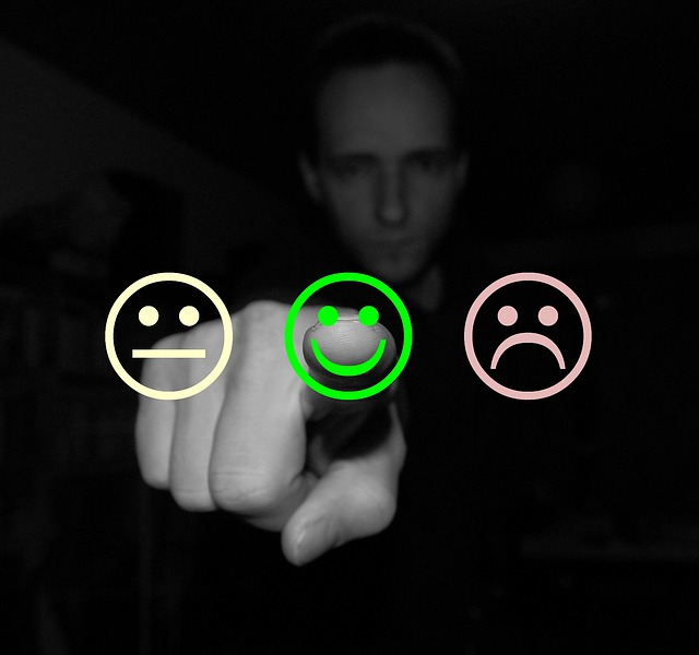 Man selection customer feedback from three different faces; happy, sad, and indifferent.