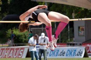 track and field runner high jumping over a pole