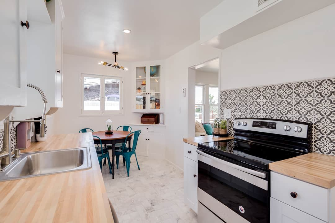 kitchen with black decorative tile and 4-person dining table