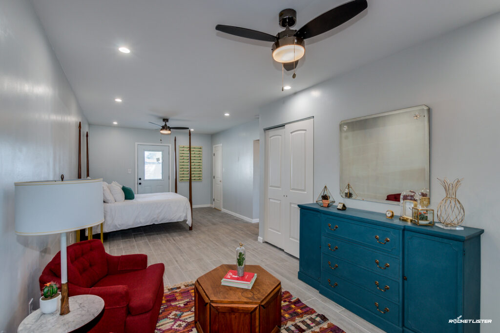 airbnb master beedroom design with red chair and four-poster bed