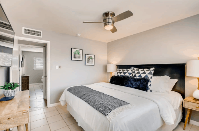 clean room design with king bed and succulent paintings on the wall