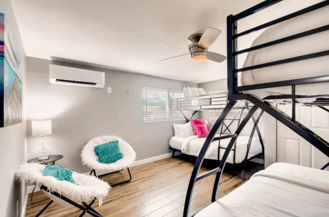 vacation rental bedroom with two bunkbeds and white chairs