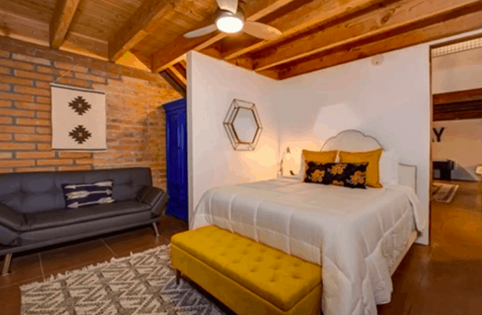 bedroom design at airbnb with yellow bench and grey couch