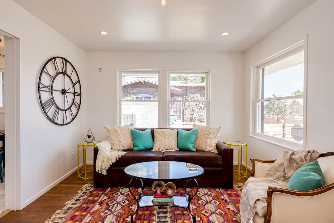 staged living room with couch large clock red rug done by honeycomb homes