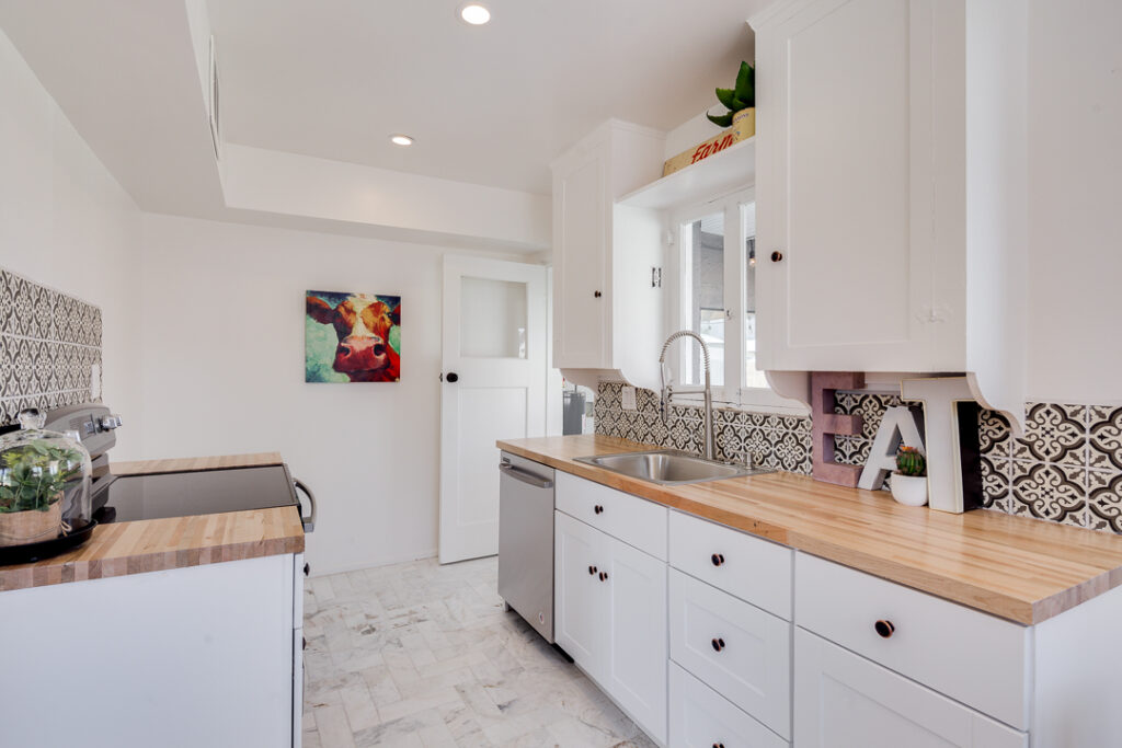 staged kitchen with patterned tile and cow painting
