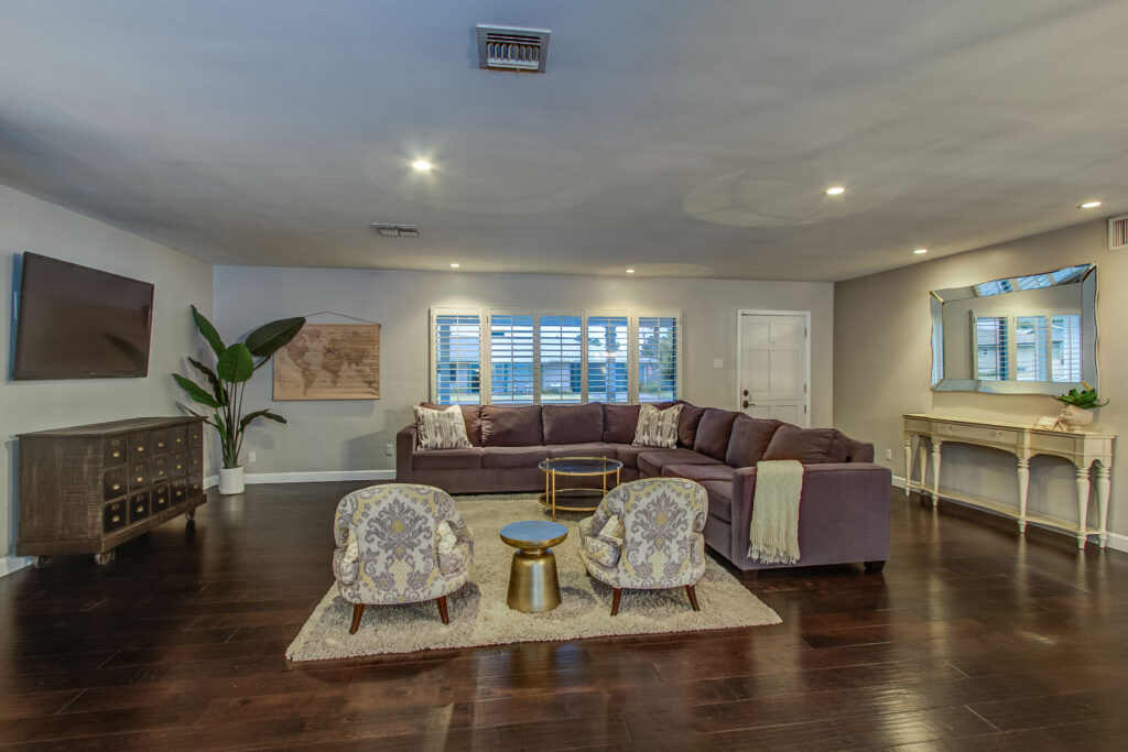 living room staged with large sectional couch and two decorative chairs