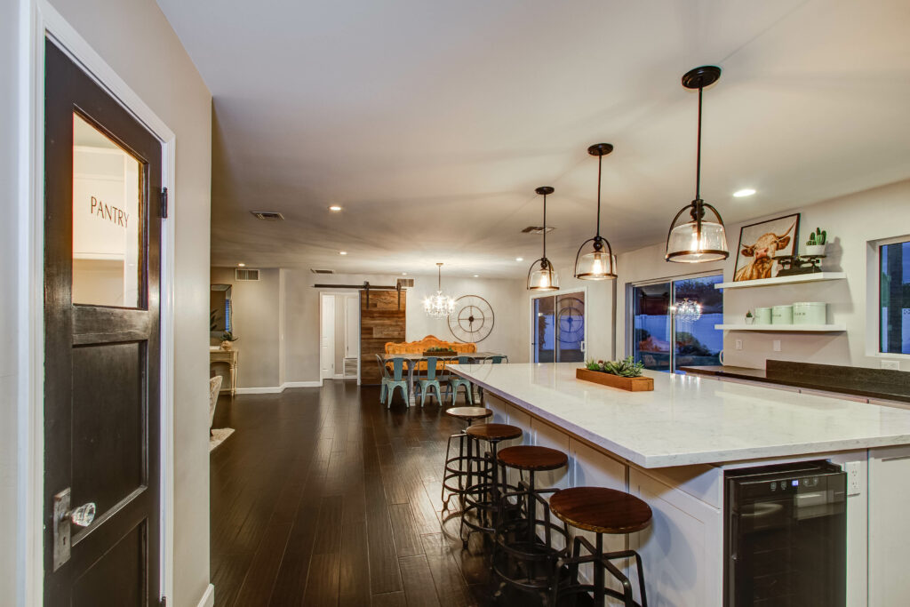 staged kitchen with large island bar stools and built-in wine fridge