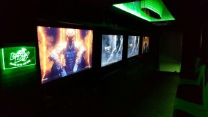 The inside of Level Up Game Truck, showing a green lit infinity mirror and 4 large gaming screens with Call of Duty.