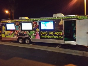 This photo shows the outside of the Level Up Game Truck with three video screens on the exterior at night time.