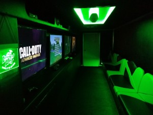 Interior display of comfortable seating, and four large screens each with a different video game