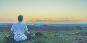 person with balanced hormones sitting at sunrise