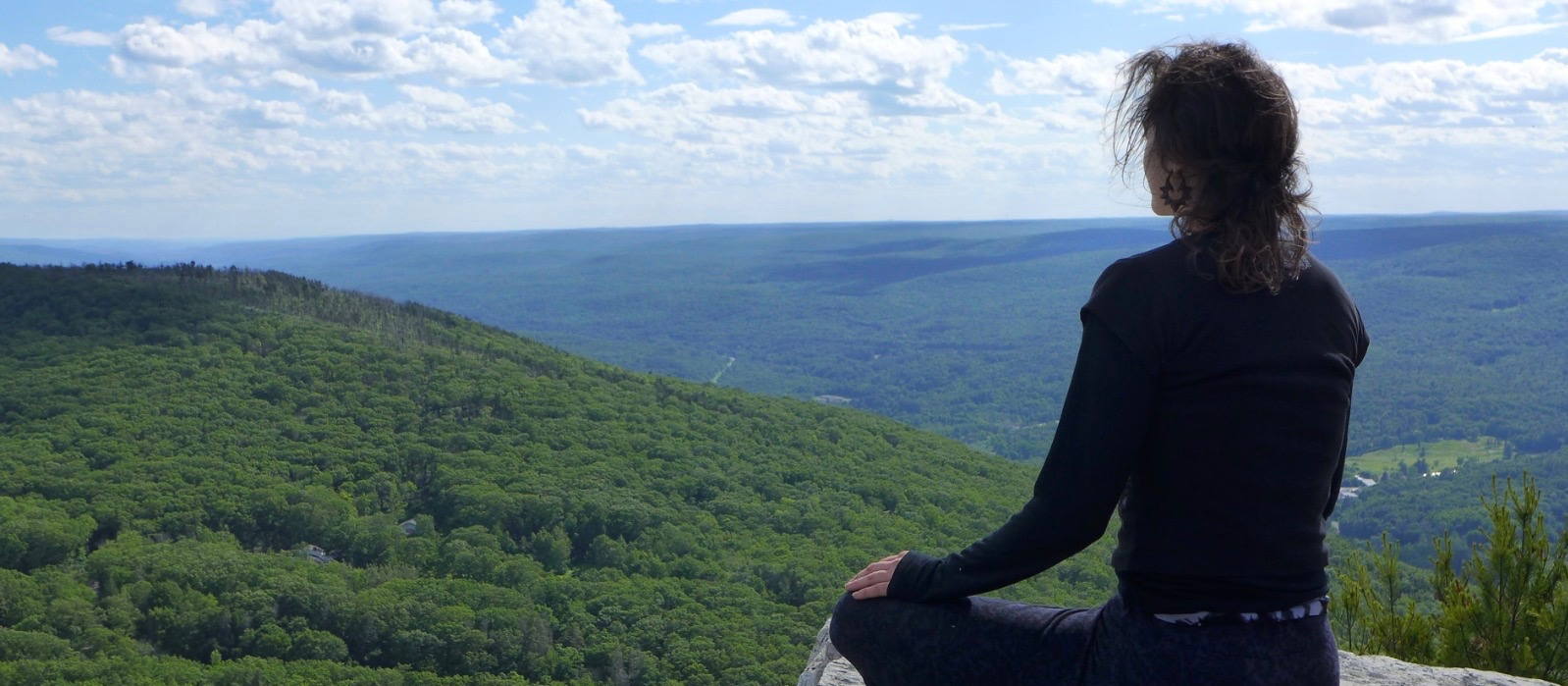 Girl meditating on a mountaintop