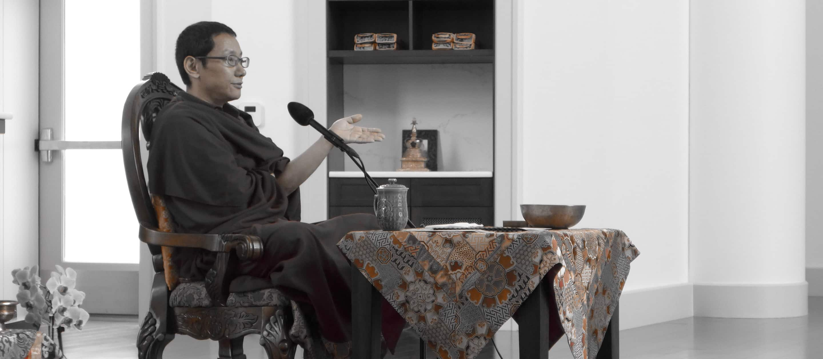 Buddhist lama at a table speaking through a microphone