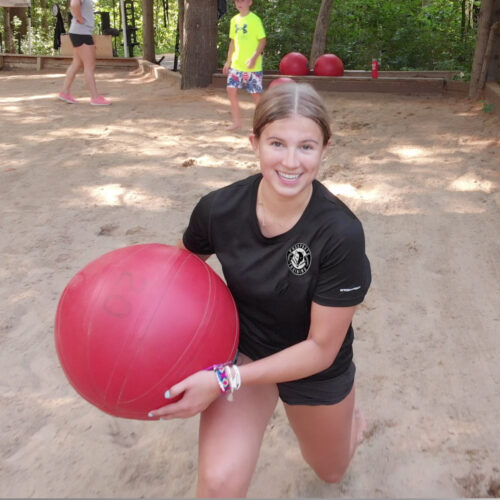 An image of a girl doing lunges with a large red water ball in the sand