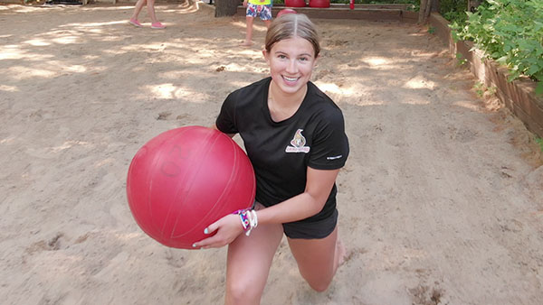 An image of a girl doing lunges in the sand holding a large red water ball