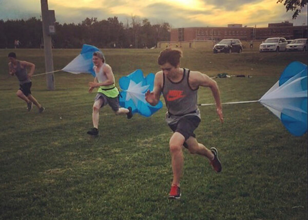 An image of athletes running with parachutes