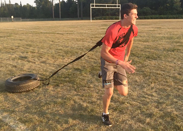 An image of a youth athlete pulling a tire as he does sprints