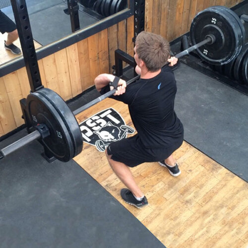 An image of a man holding a barbell on his shoulders on a lifting platform