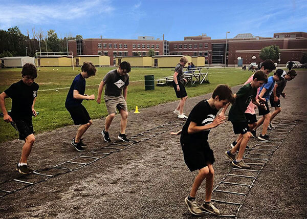 An image of youth athletes doing ladder quick feet drills