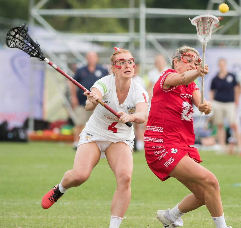 Taylor Gait scores for Canada while under pressure from Charlotte Lytollis at the 2017 FIL Rathbones Women's Lacrosse World Cup at Surrey Sports Park, Guilford, Surrey, UK, 15th July 2017 (Credit Ady Kerry).