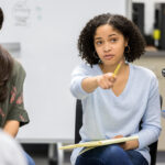 A serious female high school student sits in a circle with a group of classmates and takes a questions as she leads a study group discussion.  She uses her pencil to point to an unrecognizable classmate.